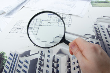 Architectural blueprints and blueprint rolls with magnifying gla