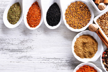 Different kinds of spices in ceramics bowls and spoons