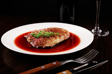 Grilled steak in wine sauce with bottle of wine