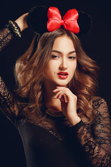 Portrait of a beautiful model with a red bow on a dark backgroun