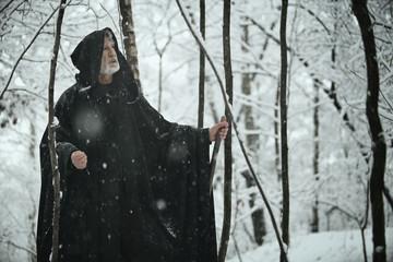 Old wise man in dark forest