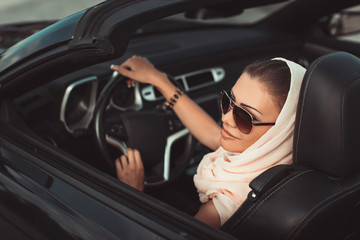 Portrait of a young lady in a black convertible.
