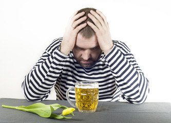 man in a vest sits on a glass of beer and thinks