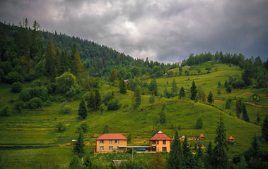 wooded Carpathians slopes with houses in center of the frame