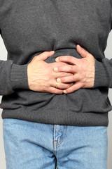 Kranker hält sich Magen/Bauch mit beiden Händen