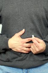 Man mit Tablette in Hand hält sich Bauch,Schmerz