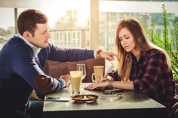 Girl is looking at watch while he is touching her hair