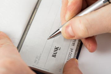 Close up shot of a cheque with a pen
