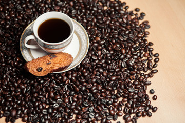 Cup of coffee with cracker on coffee beans