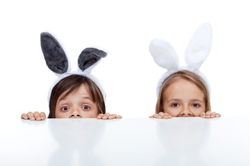 Kids with bunny ears peeking from beneath the table