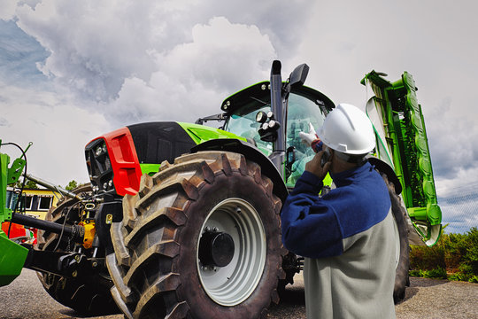mechanic pointing at giant farming tractor