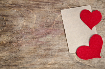 Two Red fabric hearts with sheet of paper lying on old wooden ba
