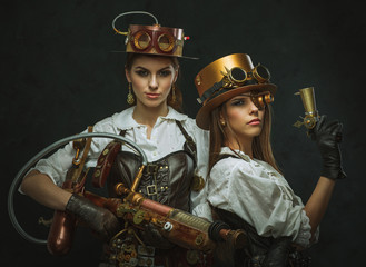 Two girls dressed in the style of steampunk with arms