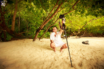 handsome groom in white holds camera on sand beach