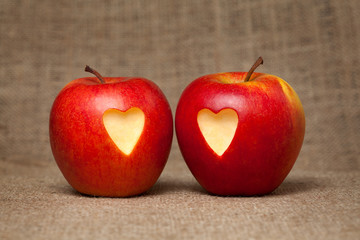 Two apples with hearts on vintage textile background