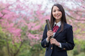 卒業証書の筒を持って笑っている女子学生