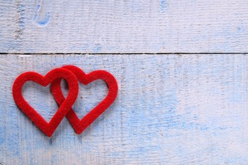 Red hearts on wooden table.