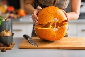 Closeup on young housewife cutting pumpkin