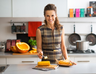 Happy young housewife rubbing boiled corn with butter