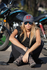 Young biker girl sitting in front of a motorcycle
