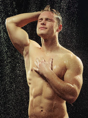 Handsome young man taking a shower