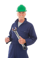 man in blue overall with green helmet and wrench
