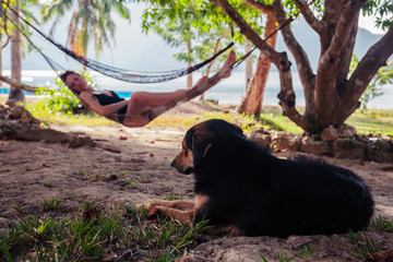 Woman relaxing in hammock with dog