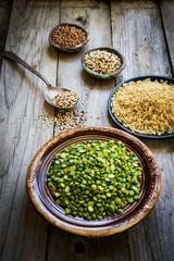 Peas,brown rice,quinoa and buckwheat on wooden background