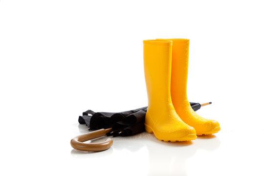 Yellow rainboots and black umbrella on white