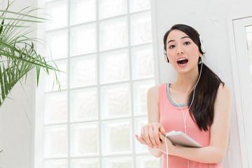 タブレットで音楽を聴く女性