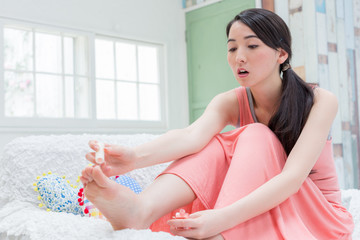 足にマネキュアを塗る女性