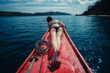 Sexy woman lying on boat in the tropics