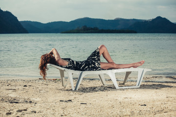 Woman relaxing on sunbed in the tropics