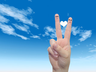 Conceptual fingers in love over blue sky
