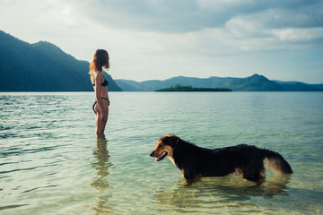 Woman with dog on tropical beach