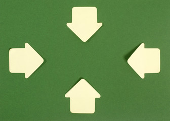 Paper arrows pointing inward. Yellow post it arrows on green.