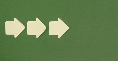 Paper arrows pointing forward. Yellow post it arrows on green.
