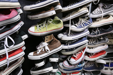 A large pile of old worn sneakers, shoes