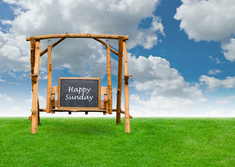 Happy Sunday on chalkboard at swing chair over grass field with