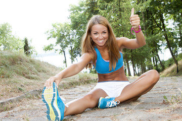 Obraz Fit woman stretching her leg outdoor - fototapety do salonu