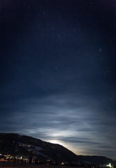 mountain silhouette against starry nigh sky and shining moon