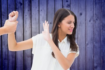 Composite image of fearful brunette being grabbed by the hand