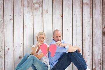 Composite image of sad mature couple holding a broken heart