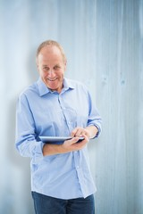 Composite image of happy mature man using his tablet pc