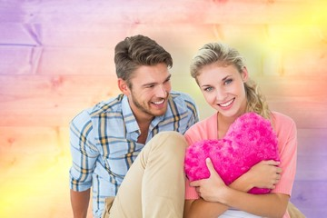Wall Mural - Attractive young couple sitting holding heart
