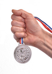 Vencedor celebrando triunfo sujetando una medalla de plata.