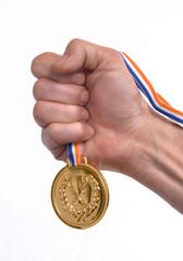 Vencedor celebrando triunfo sujetando una medalla de oro.