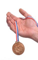 Vencedor celebrando triunfo sujetando una medalla de bronce.