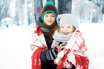 children boy and girl play together in a snowy winter park