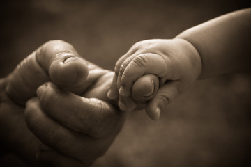 Baby hand holding mother finger with retro effect